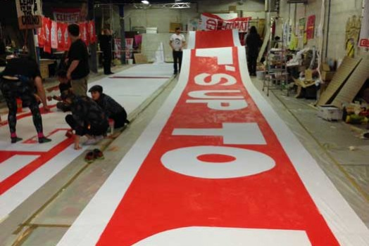 Painting 300 ft. banner for D12 demos in Paris